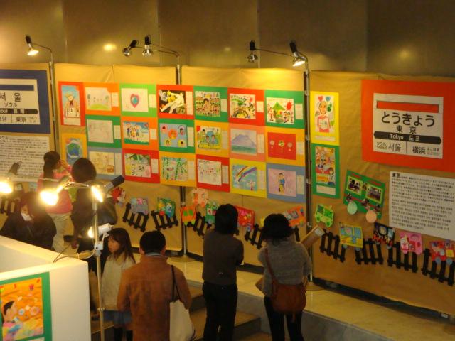 2011年東京の展示会で共同制作「ともだち列車」に見入る来場者